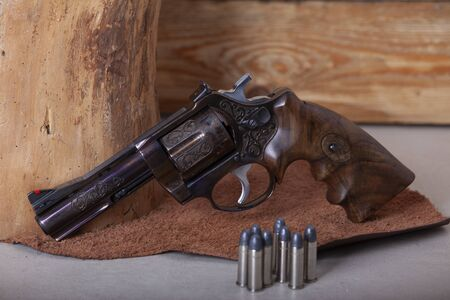 old style revolver handgun photographed on the leather background