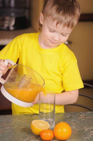 The child in a yellow vest drinks  orange juice photo