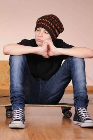 The teenager with a skateboard and in a hat photo