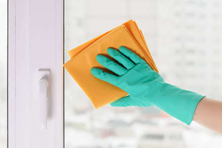 work glove: The hand in a green glove washes a window
