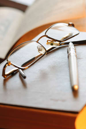 Glasses and the pen lay on the old book photo