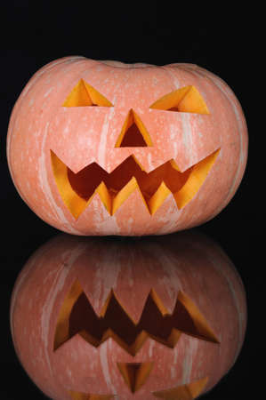 pumpkin with lighting candle inside on black background photo