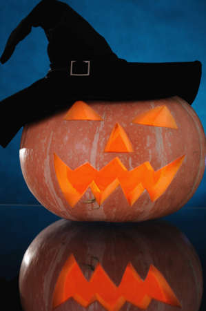 darck:  pumpkin with lighting candle inside on darck blue background