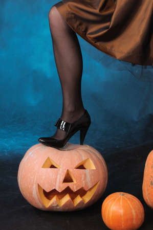 The leg of a witch costs on a pumpkin photo