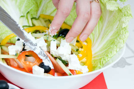 Preparation of salad from cheese and fresh vegetables
