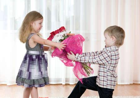 De kleine jongen geeft aan het meisje een bos van bloemen
