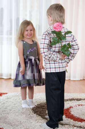 The little boy gives to the girl a  flowers photo