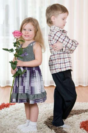 De kleine jongen geeft aan het meisje een bloemen