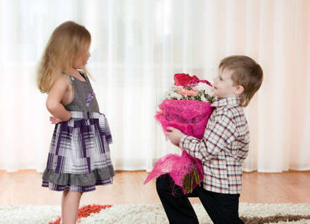 The little boy gives to the girl a bunch of flowers photo