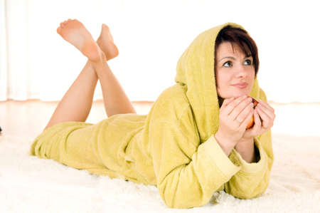 red bathrobe: Woman in robe with  apple lying on the floor