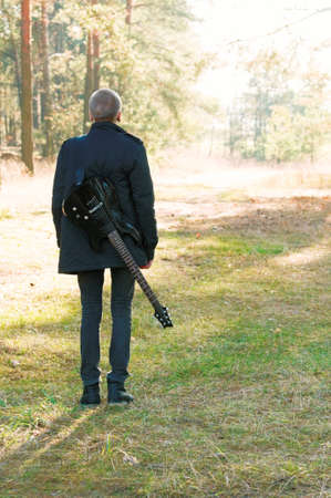 teen musician with a guitar in the autumn forest photo