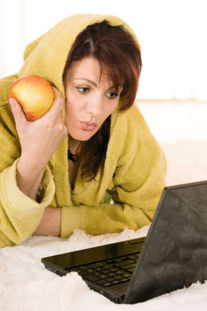 red bathrobe: Woman in robe with laptop and apple lying on the floor