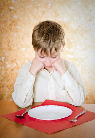 empty bowl: pensive child looks at the empty plate Stock Photo