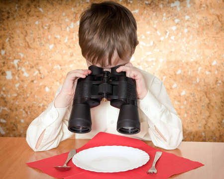 child looks at a plate throught a binoculars photo
