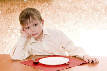 ni�os pobres: infantil pensativa se sienta cerca de un plato vac�o y mira hacia adelante Foto de archivo