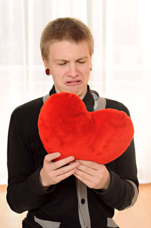 frustrated teenager  with a teddy heart in hand photo