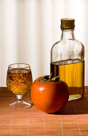 persimmon and a bottle of whiskey is on the table photo