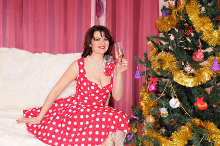 woman pin-up sits near fir-tree with wineglass photo