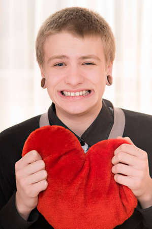 frustrated teenager  with a plush heart in hand photo