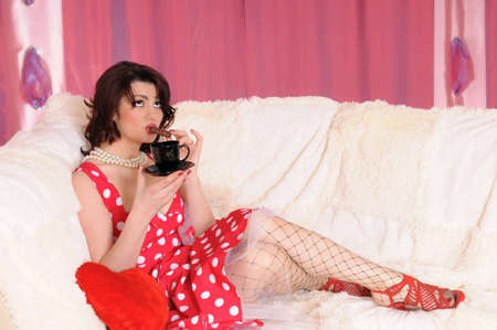 woman pin-up in red dress sit on the sofa with tea photo
