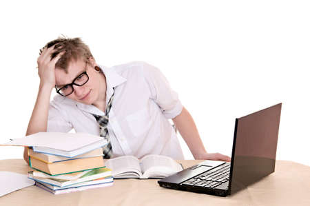 frustrated student sits behind a desk isolated on white background photo