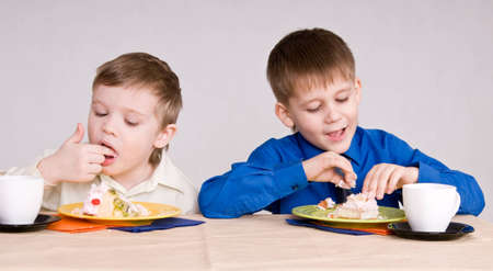 two boys eating a cake his hands photo