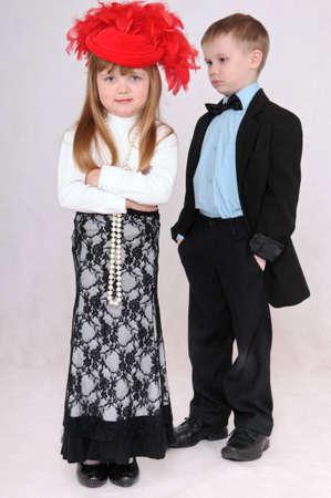 niño y niña: muchacha triste en un sombrero rojo la espera de una disculpa de parte del niño Foto de archivo