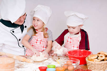teaches: Chef teaches children to knead the dough Stock Photo