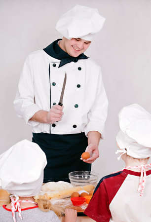Chef is teaching kids to cook on the grey background photo