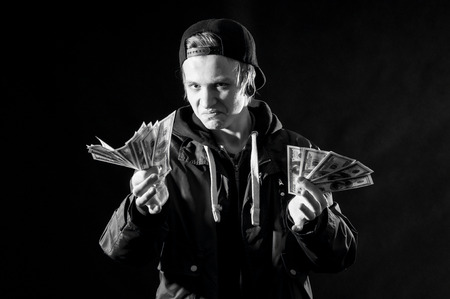 a young man with money in hands on dark background photo