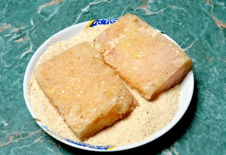 breading: raw fish fillet on a plate in breading