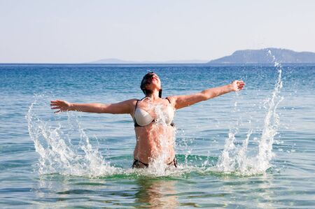 emerge: happy woman in sea water splashes
