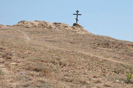 lifeless: wooden cross on a lifeless dry hill