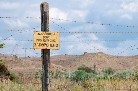 barbed wire fence: pillar with a prohibition sign and barbed wire fence