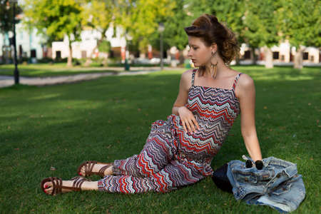 glases: Pregnant woman lying on green grass outdoors. Wearing glases model summer look. Having fun. Motherhood. Maternity.