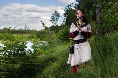 lamentable: Sad cute farmgirl looking far away near river, wearing traditional dress, holding harebells flowers. Stock Photo