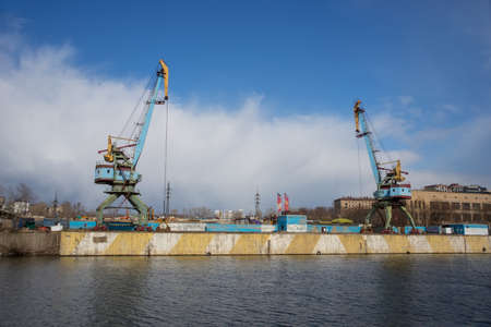 dockside: Two old crane loading cargo in the river port, moscow river