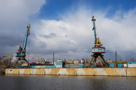 lading: Two old crane loading cargo in the river port, moscow river