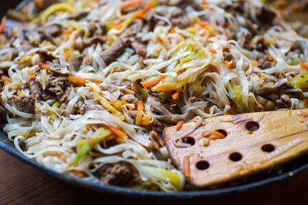 伝統的なアジア牛肉と野菜の鍋と木のへら