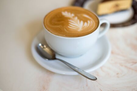 cappuchino: Cappuchino or latte coffe in a white cup on with a cake on a light beige table. Stock Photo