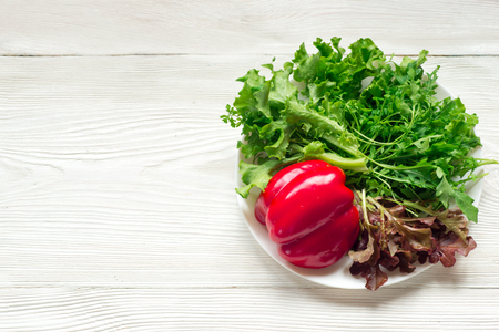 Fresh mixed green salad with red pepper on white plate on wooden table close up