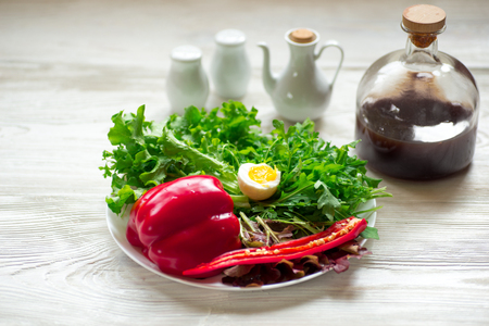Green salad with arugula, salad,  basil, red pepper, boiled egg on rustic wooden background, top view.