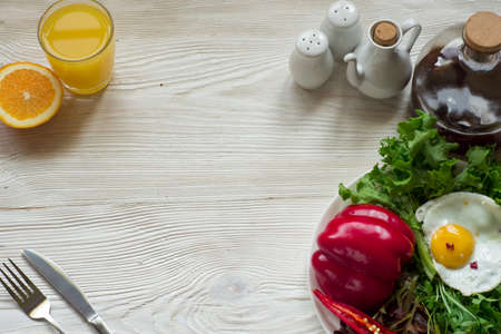 Green salad with arugula, salad,  basil, red pepper, baked egg on rustic wooden background, top view. Imagens
