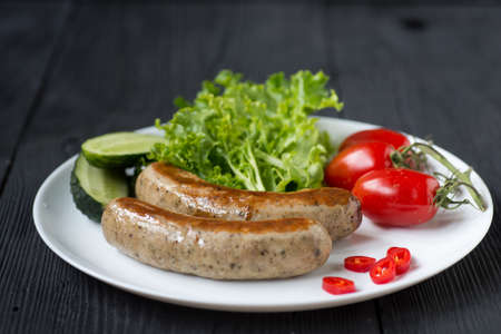 Healthy Breakfast - sausages, tomato, salad and cucumber on black background Standard-Bild