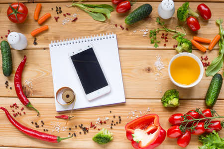 wooden metre: Table with white notebook and Variety of fresh vegetables, tomato, pepper, cucumber, carrot, space for text on white. Stock Photo