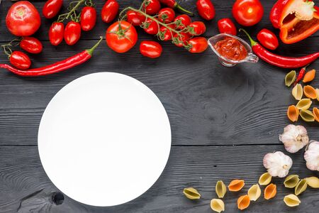 photography background: Healthy food background and Copy space  studio photography of raw tomatos  on black wooden table. Top view.