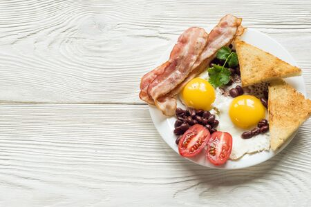 bacon baked beans: English breakfast with bacon, sausage, fried egg, baked beans on white plate
