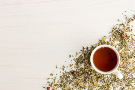 catnip: Cup of herbal tea and linden and Melissa flowers, bright wooden table, high angle view