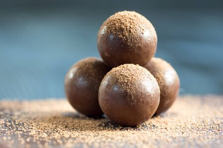 Multiple chocolate ball candies composition, isolated over the dark background.