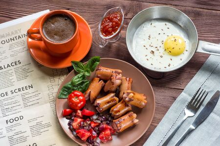 flemish: Traditional breakfast - fried eggs, sausages, tomato, beans,  onions, Basil. Selective focus